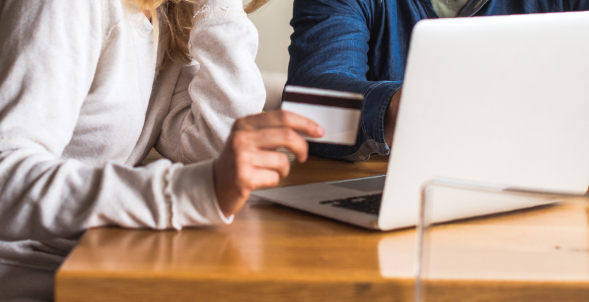 A close up of a couple using a debit card while on a laptop