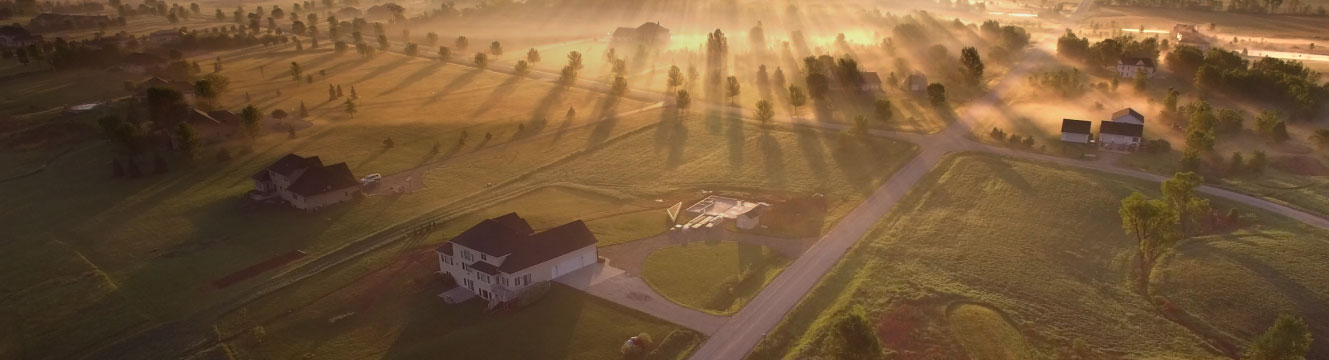 An aerial view of a rural community with the rising sun shining through fog.