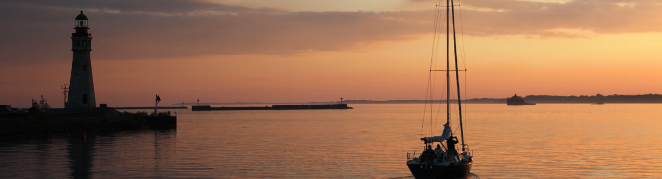 A view of a sunset over Lake Erie with a shadowed lighthouse and a sailboat.